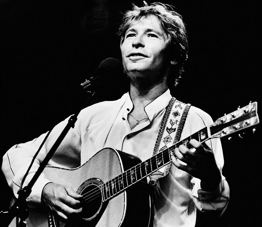 Singer John Denver performs during an outdoor concert in Boston in 1983. (AP Photo/Keith Jacobson)