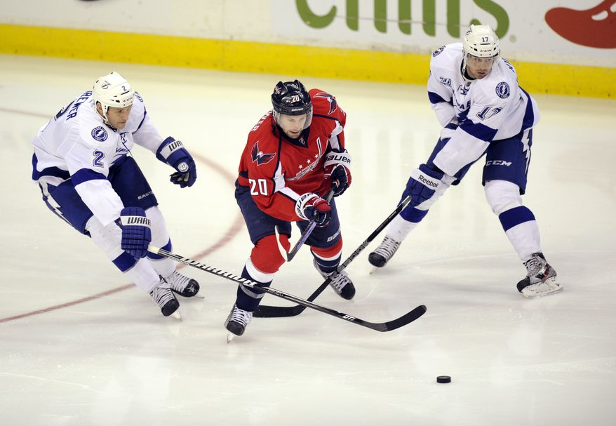 Washington Capitals right wing Troy Brouwer (20) battles for the puck against Tampa Bay Lightning defenseman Eric Brewer (2) and Tampa Bay Lightning center Alex Killorn (17) during the third period of an NHL hockey game, Sunday, April 7, 2013, in Washington. The Capitals won 4-2. (AP Photo/Nick Wass)