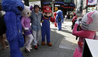 A man is has his photo taken by a Hello Kitty character (right) as he poses with Cookie Monster, another Hello Kitty and Super Mario characters in New York's Times Square on Tuesday, April 9, 2013. A string of arrests in the past few months has brought unwelcome attention to the growing number of people, mostly poor immigrants, who make a living by donning character outfits, roaming Times Square and charging tourists a few dollars to pose with them in photos. (AP Photo/Richard Drew)