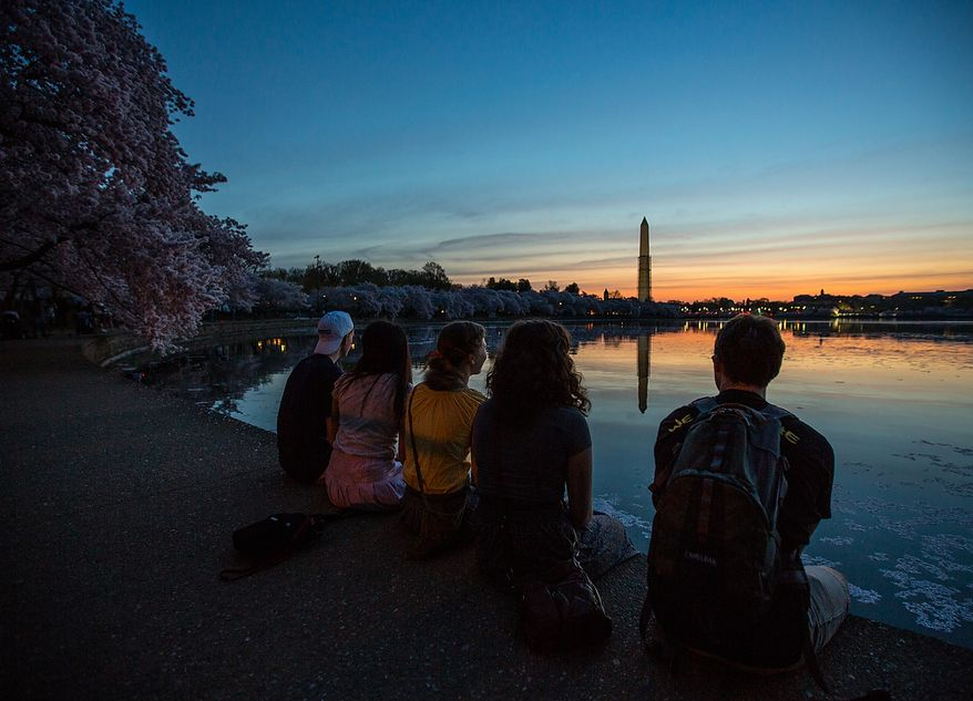 Students visiting the district, sit on the edge of the tidal basin as they watch the sunrise in Washington, DC., Thursday, April 11, 2013. (Andrew S Geraci/The Washington Times)