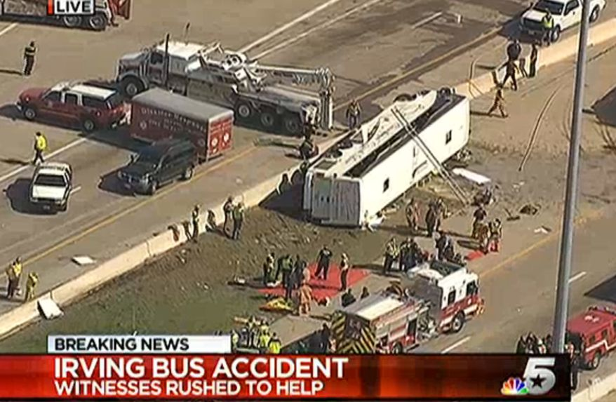 This frame grab provided by KXAS-TV shows emergency personnel at the scene where a chartered bus overturned on a highway near Dallas-Fort Worth International Airport in Irving, Texas. (AP Photo/KXAS-TV)