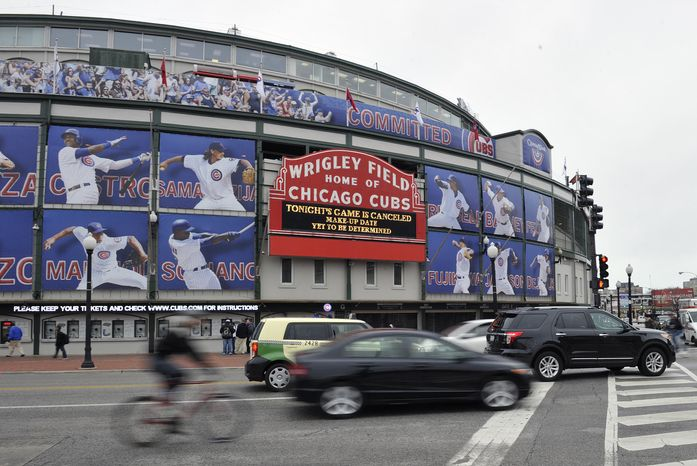 Traffic drives past Wrigley Field after the baseball game between the Milwaukee Brewers and Chicago Cubs was postponed due to inclement weather on Wednesday, April 10, 2013, in Chicago. (AP Photo/Jim Prisching)