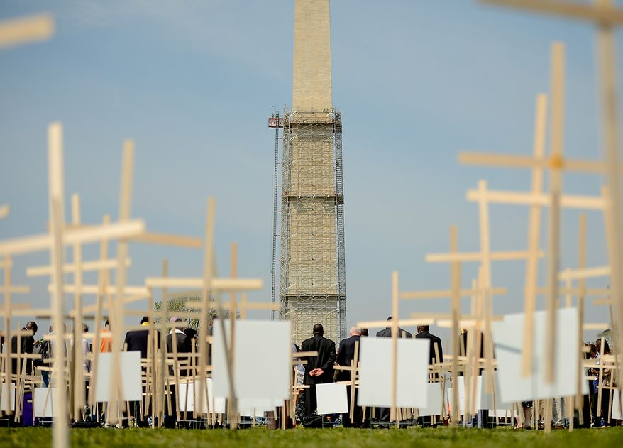 Thousands of grave markers are placed in the ground to represent victims of gun violence as religious leaders around the country begin a 24-hour vigil on the National Mall to honor the victims of gun violence since the school shooting in Newtown, Conn., Washington, D.C., Thursday, April 11, 2013. (Andrew Harnik/The Washington Times)