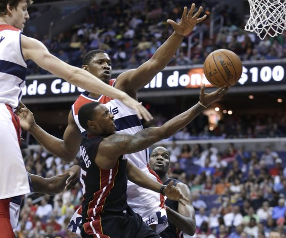 Miami Heat guard Mario Chalmers, center, drives to the basket against Washington Wizards forward Jan Vesely, left, and center Kevin Seraphin during the first half of an NBA basketball game Wednesday, April 10, 2013, in Washington. (AP Photo/Evan Vucci)