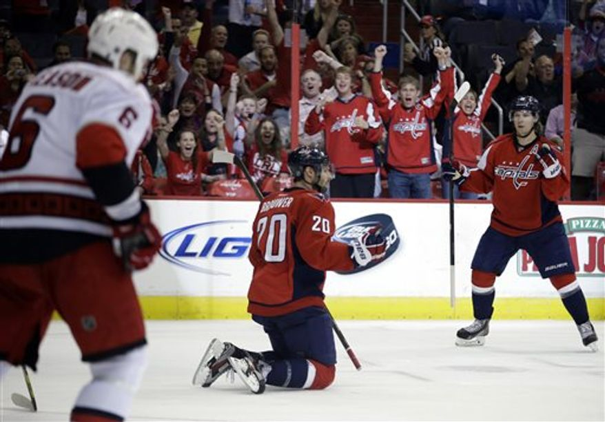 Washington Capitals center Nicklas Backstrom, right, celebrates a goal by teammate Troy Brouwer, center, as Carolina Hurricanes defenseman Tim Gleason skates off during the second period of an NHL hockey game on Thursday, April 11, 2013, in Washington. (AP Photo/Evan Vucci)