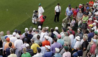 Bubba Watson hits out of the crowd on the fourth fairway during the first round of the Masters golf tournament Thursday, April 11, 2013, in Augusta, Ga. (AP Photo/Charlie Riedel)