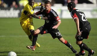 Columbus Crew foward Dominic Oduro (11) goes for the ball against D.C. United midfielder/defender Perry Kitchen (23) and Daniel Woolard, right, during the second half of an MLS soccer game, Saturday, March 23, 2013, in Washington. Columbus won 2-1. (AP Photo/Nick Wass)