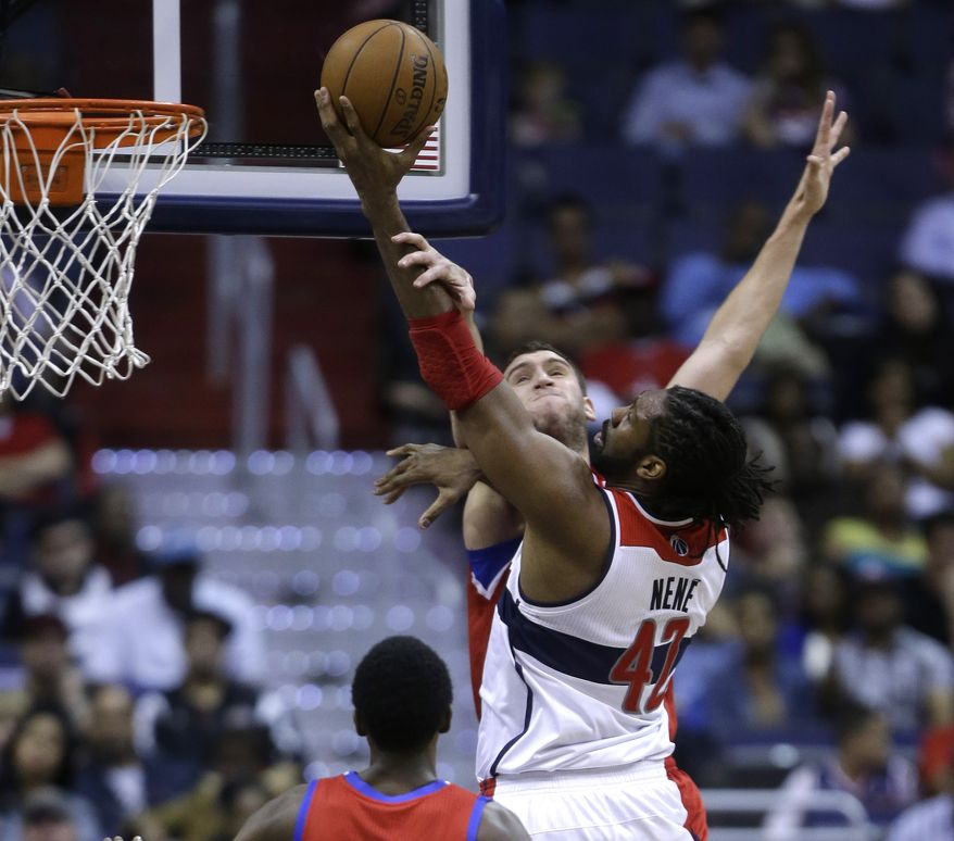 Washington Wizards center Nene, right, drives to the basket against Philadelphia 76ers center Spencer Hawes during the first half of an NBA basketball game on Friday, April 12, 2013, in Washington. (AP Photo/Evan Vucci)