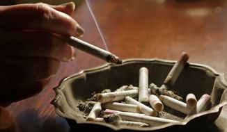 **FILE** A woman smokes a cigarette at her home in Alabama on March 2, 2013. (Associated Press)