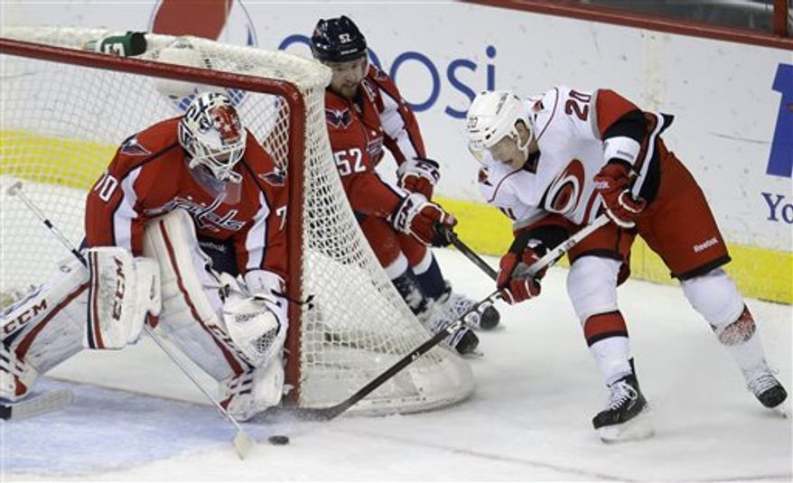 Washington Capitals goalie Braden Holtby, left, makes a save against Carolina Hurricanes center Riley Nash, right, as defenseman Mike Green looks on during the first period of an NHL hockey game on Thursday, April 11, 2013, in Washington. (AP Photo/Evan Vucci)