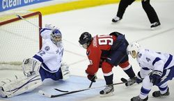 Washington Capitals center Marcus Johansson (90) has his stick broken against Tampa Bay Lightning center Vincent Lecavalier (4) during the overtime period of an NHL hockey game, Saturday, April 13, 2013, in Washington. The Capitals won 6-5 in overtime. Also seen is Lightning goalie Mathieu Garon (32). (AP Photo/Nick Wass)