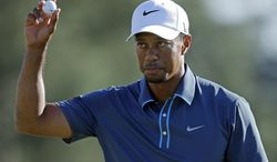Tiger Woods holds up his ball after putting out on the 18th hole during the third round of the Masters golf tournament Saturday, April 13, 2013, in Augusta, Ga. (AP Photo/David Goldman)