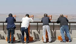 Visitors use binoculars to scan North Korean territory from the vantage point of the unification observation post near the border village of Panmunjom separating North and South Korea. (Associated Press)