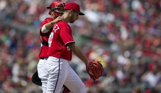 Washington Nationals catcher Kurt Suzuki, left, talks with pitcher Gio Gonzalez during the first inning of a baseball game at Nationals Park on Sunday, April 14, 2013, in Washington. (AP Photo/Evan Vucci)