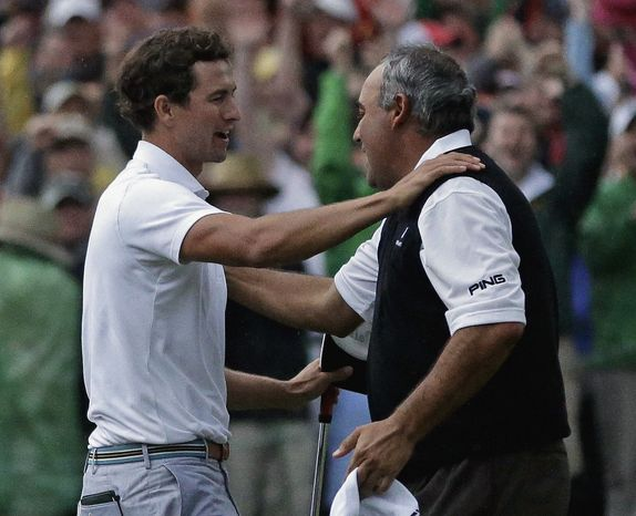 Adam Scott, of Australia, hugs Angel Cabrera, of Argentina, after making a birdie putt on the second playoff hole to win the Masters golf tournament Sunday, April 14, 2013, in Augusta, Ga. (AP Photo/David J. Phillip)