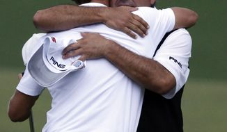 Angel Cabrera, right, of Argentina, hugs Adam Scott, of Australia, after Scott made a birdie putt on the second playoff hole to win the Masters golf tournament Sunday, April 14, 2013, in Augusta, Ga. (AP Photo/David Goldman)
