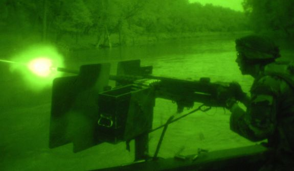 US Naval Special Warfare Combatant-crew Crewman fires a 50 caliber machine gun from Riverine boat in the darkness of night, as seen through night vision goggles.  Photo: (C) 2011 Greg E. Mathieson Sr. / NSW Publications, LLC