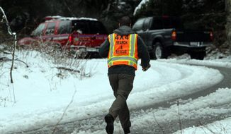 An official with King County Search and Rescue runs toward the scene of an avalanche near Snoqualmie Pass in Washington state on Saturday, April 13, 2013. (Ken Lambert/The Seattle Times)