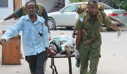 Somali soldiers carry a wounded civilian from the entrance of the Supreme Court complex after being injured during a siege by militants in Mogadishu, Somalia, on Sunday, April 14, 2013. (AP Photo/Farah Abdi Warsameh)