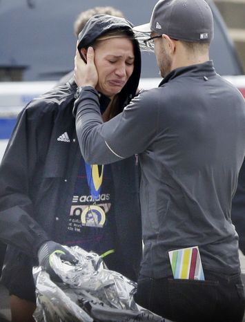 An unidentified Boston Marathon runner is comforted as she cries in the aftermath of two blasts which exploded near the finish line of the Boston Marathon in Boston, Monday, April 15, 2013. (AP Photo/Elise Amendola)