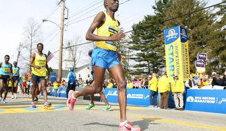 Defending champion Wesley Korir, of Kenya, warms up prior to the start of the 117th running of the Boston Marathon, in Hopkinton, Mass., Monday, April 15, 2013. (AP Photo/Stew Milne)