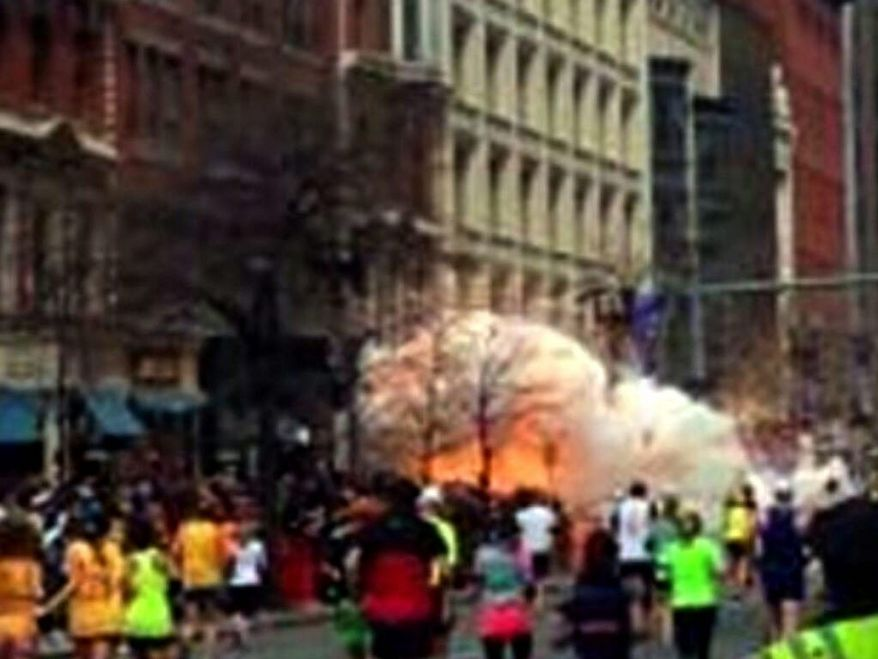 ** FILE ** In this image from video provided by WBZ TV, spectators and runners run from what was described as twin explosions that shook the finish line of the Boston Marathon, Monday, April 15, 2013, in Boston. Two explosions shattered the euphoria of the Boston Marathon finish line on Monday, sending authorities out on the course to carry off the injured while the stragglers were rerouted away from the smoking site of the blasts. (AP Photo/WBZTV)