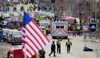 Emergency workers aid injured people at the finish line of the 2013 Boston Marathon following an explosion in Boston, Monday, April 15, 2013. (AP Photo/Charles Krupa)