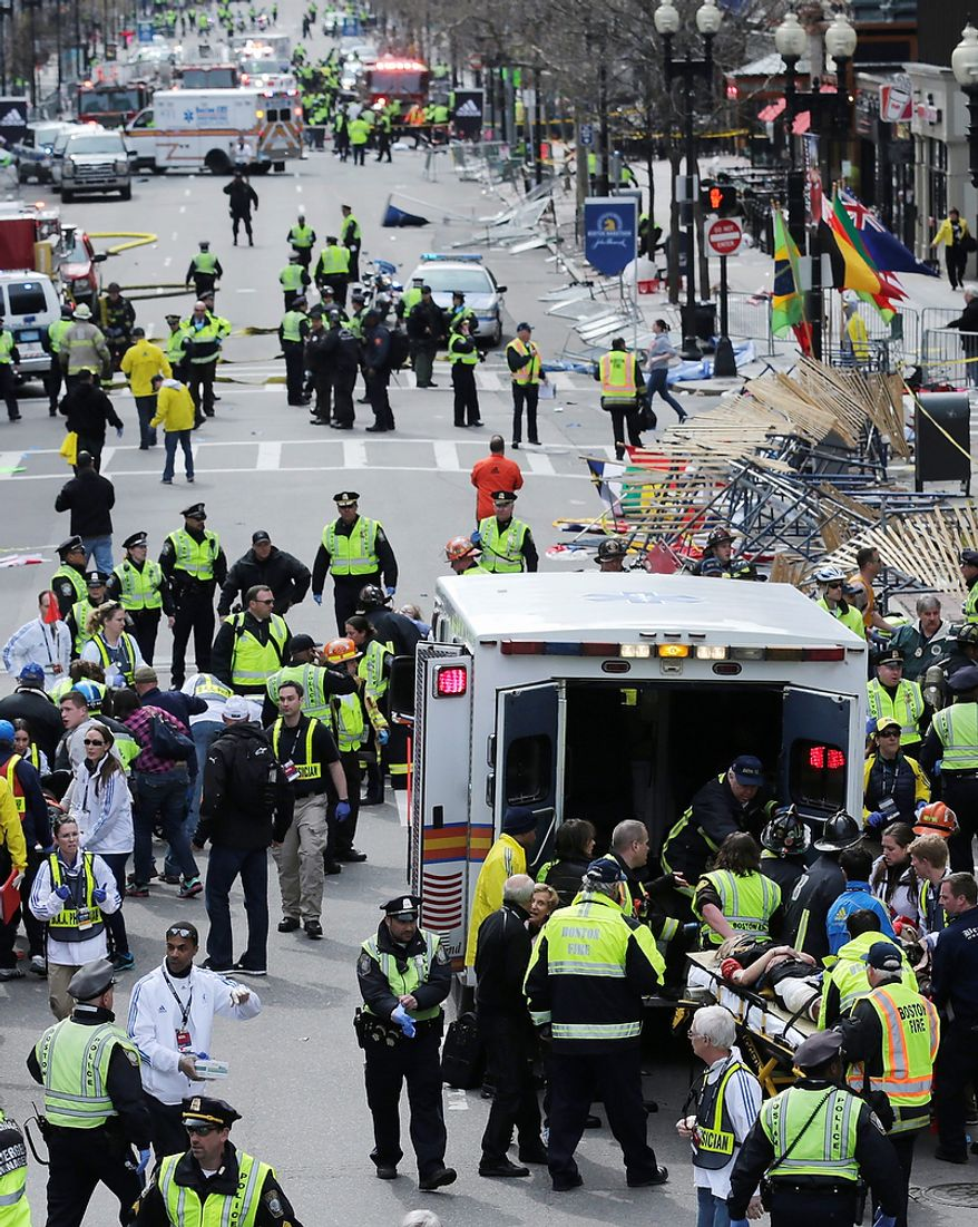 Medical workers aid injured people at the finish line of the 2013 Boston Marathon following an explosion in Boston, Monday, April 15, 2013. Two explosions shattered the euphoria of the Boston Marathon finish line on Monday, sending authorities out on the course to carry off the injured while the stragglers were rerouted away from the smoking site of the blasts. (AP Photo/Charles Krupa)