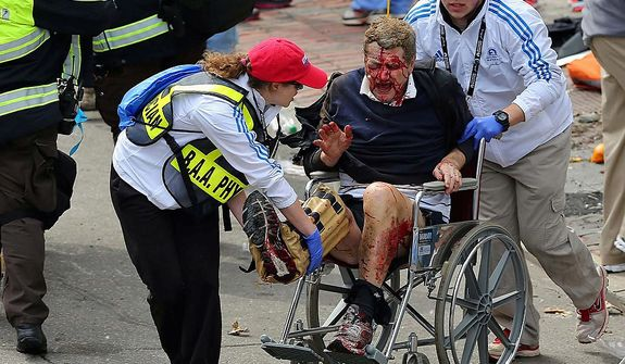 Medical workers aid an injured man at the 2013 Boston Marathon following an explosion in Boston, Monday, April 15, 2013. Two bombs exploded near the finish of the Boston Marathon on Monday, killing at least two people, injuring at least 22 others and sending authorities rushing to aid wounded spectators. (AP Photo/The Boston Globe, David L. Ryan)
