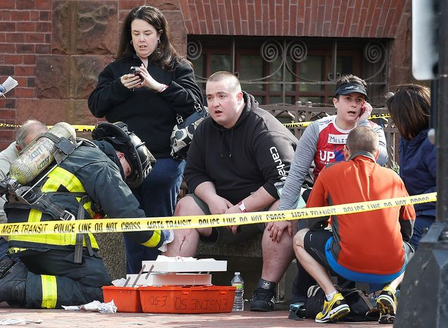 ** FILE ** A firefighter tends to an injured man following an explosion near the finish line of the Boston Marathon in Boston, Monday, April 15, 2013. (AP Photo/Michael Dwyer)