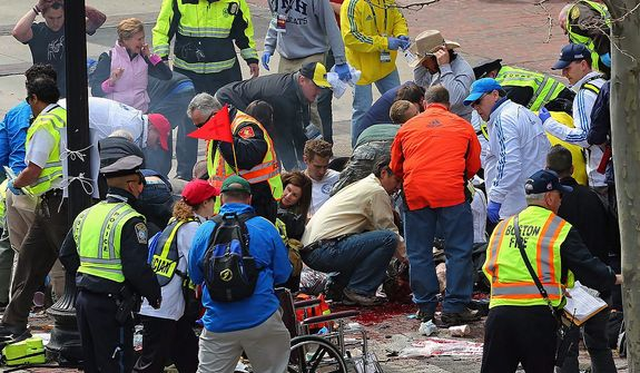 Medical workers aid injured people at the 2013 Boston Marathon following an explosion in Boston on Monday, April 15, 2013. Two explosions shattered the euphoria at the marathon's finish line on Monday, sending authorities out on the course to carry off the injured while the stragglers were rerouted away from the smoking site of the blasts. (AP Photo/The Boston Globe, David L Ryan)