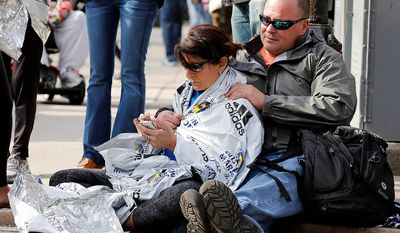 Chris Darmody, right, holds his wife Sue in Boston, Monday, April 15, 2013. Chris says he was waiting for Sue when an explosion detonated near his location at the finish line of the Boston Marathon. The couple were later reunited after all runners were diverted from the course. (AP Photo/Michael Dwyer)