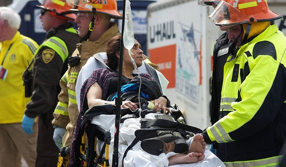 Emergency responders aid a woman on a stretcher who was injured in a bomb blast near the finish line of the Boston Marathon Monday, April 15, 2013 in Boston. Two bombs exploded in the packed streets near the finish line of the marathon on Monday, killing at least two people and injuring more than 80, authorities said. (AP Photo/Jeremy Pavia)
