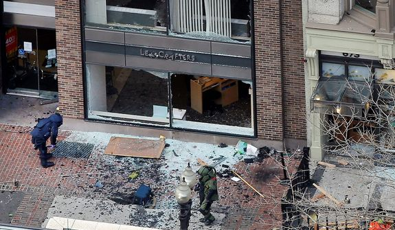 ** FILE ** One of the blast sites on Boylston Street near the finish line of the 2013 Boston Marathon is investigated by two people in protective suits in the wake of two blasts in Boston Monday, April 15, 2013. (AP Photo/Elise Amendola)