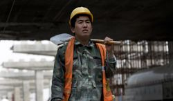 A worker prepares to construct a city highway which is under construction in Beijing on April 15, 2013. China's economic growth slowed unexpectedly in the first three months of the year, fueling concern about the strength of its shaky recovery. (Associated Press)