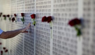 Mideast wars veteran touches the wall of names at the Armored Corps memorial for fallen soldiers after a ceremony marking the annual Memorial Day for soldiers and civilians killed in more than a century of conflict between Jews and Arabs, in Latrun near Jerusalem, Israel, Monday, April, 15, 2013. Israel says 23,085 security personnel have been killed since 1860, when Jews began moving back to the area. (AP Photo/Ariel Schalit)