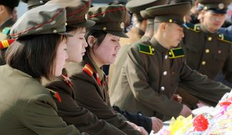 North Korean soldiers offer flowers for North Korean late leaders Kim Il-sung and Kim Jong-il at Mansu Hill in Pyongyang, North Korea, Monday, April 15, 2013. (AP Photo/Kyodo News)