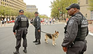 Homeland Security police officers keep watch along Pennsylvania Avenue a day after the Boston Marathon bombings. Ayo Handy-Kendi (left) and others wear chains to show their opposition to the District not having a voting representative in Congress.