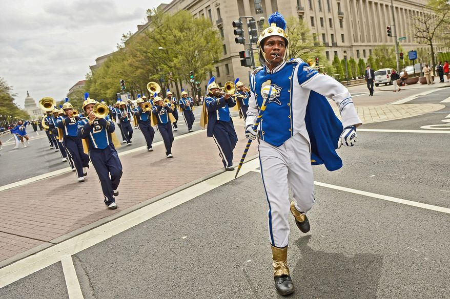 Ballou High School drum major Genuine Kensey leads the school's marching band down Pennsylvania Avenue during Tuesday's Emancipation Day parade. (Photographs by Andrew Harnik/The Washington Times)