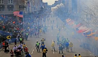 People react as an explosion goes off near the finish line of the 2013 Boston Marathon in Boston on Monday, April 15, 2013. Two explosions went off near the finish line, sending authorities out on the course to carry off the injured while the stragglers were rerouted away from the smoking site of the blasts. (AP Photo/The Boston Globe, David L Ryan)