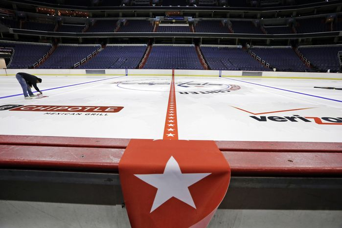 **FILE** A worker appears on the ice as logos are placed and the lines painted in preparation for the Washington Capitals upcoming NHL hockey season at V