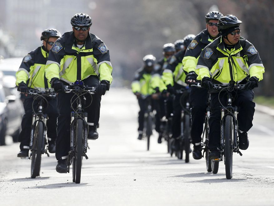 Boston police on bicycles patrol on Commonwealth Avenue following the explosions at the finish line of the Boston Marathon in Boston on Monday, April 15, 2013. (AP Photo/Michael Dwyer)