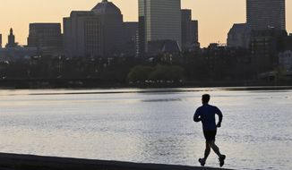 ** FILE ** A solitary runner heads along the banks of the Charles River in Cambridge, Mass., in front of the Boston skyline, at dawn on Tuesday, April 16, 2013, after explosions killed three and injured more than 140 at the Boston Marathon the day before. (AP Photo/Charles Krupa)