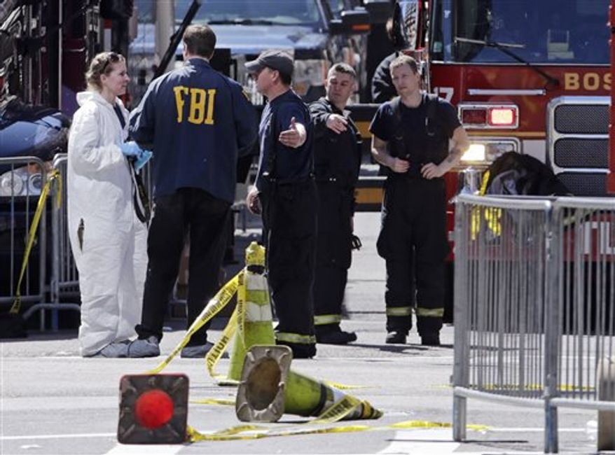 Boston firefighters, right, talk with FBI agents and a crime scene photographer at the scene of Monday's Boston Marathon explosions, which killed at least three and injured more than 140, in Boston, Tuesday, April 16, 2013. The bombs that blew up seconds apart near the finish line left the streets spattered with blood and glass, and gaping questions of who chose to attack at the Boston Marathon and why. (AP Photo/Charles Krupa)