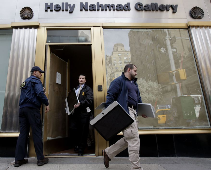 Federal agents remove items, including computers, from an art gallery in New York on Tuesday, April 16, 2013, as part of an investigation into what federal authorities say was high-stakes poker games attended by professional athletes, Hollywood celebrities and Wall Street titans and run by members of Russian organized crime. (AP Photo/Seth Wenig)