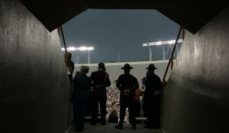 **FILE** Security personnel watch over the crowd during an undergraduate graduation ceremony at Virginia Tech in Lane Stadium in Blacksburg, Va., Friday, May 11, 2007. (AP Photo/Carolyn Kaster)