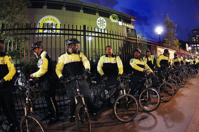 **FILE** Boston police officers on bicycles assemble outside TD Garden in Boston Wednesday, June 15, 2011, as Game 7 of the NHL hockey Stanley Cup Finals between the Boston Bruins and the Vancouver Canucks is played in Vancouver, British Columbia. (AP Photo/Elise Amendola)