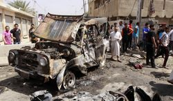 Civilians gather at the scene of a car bomb attack in the east Baghdad neighborhood of Kamaliya, Iraq, on Monday, April 15, 2013. A series of attacks across, Iraq many involving car bombs, has killed and wounded dozens of people, police said, less than a week before Iraqis in much of the country are scheduled to vote in the country's first elections since the 2011 U.S. troop withdrawal. (AP Photo/ Khalid Mohammed)