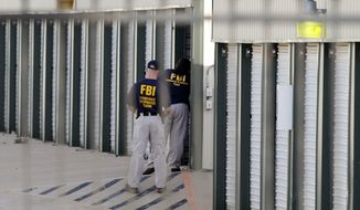 "Authorities search a storage unit at Gibson Self Storage as they continue to investigate the slayings of Kaufman County District Attorney Mike McLelland, his wife and a top prosecutor, Saturday, April 13, 2013, in Seagoville, Texas. Authorities investigating the death of a Texas district attorney arrested Eric Williams, a former justice of the peace and charged him Saturday with making a ""terroristic threat"" after searching his home. (AP Photo/The Dallas Morning News, Michael Ainsworth)"