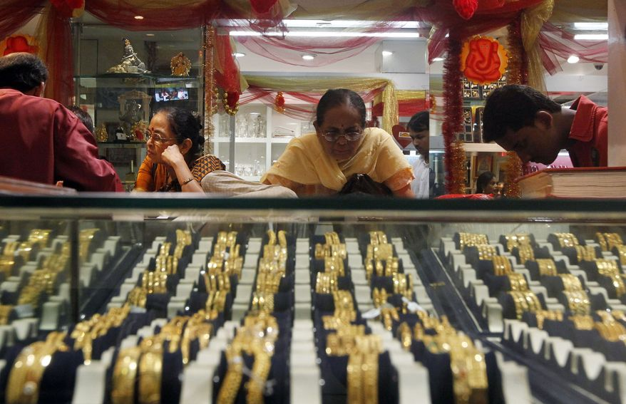 An Indian woman looks at a display of gold jewelry at a shop in Mumbai on Thursday, Feb. 14, 2013. The price of gold has plunged, suggesting that a decade-long surge in the precious metal is over. (AP Photo/Rajanish Kakade)